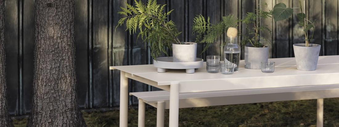 Banc et table en acier linéaire en blanc de Muuto dans la vue d'ambiance. Grâce à leur construction en acier, la table et le banc s'intègrent parfaitement dans le jardin et inspirent par leur design moderne.