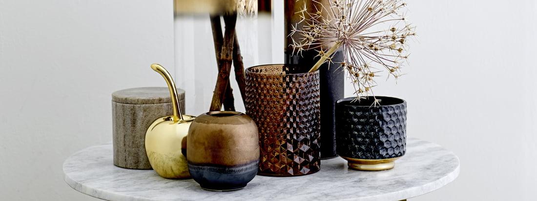 Le photophore en verre, le vase en verre d'une hauteur de 35 cm, le cerisier décoratif et la boîte de rangement en marbre de Bloomingville ont fière allure sur une table d'appoint ronde.