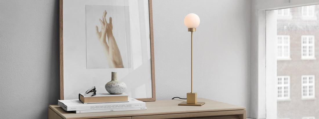 Snowball lampe de table H 41 cm, laiton par Northern dans la vue d'ambiance. Utilisée comme lampe de travail sur le bureau ou comme éclairage d'arrière-plan dans le salon sur le buffet, la lumière de la lampe de table Snowball crée une atmosphère chaleureuse dans la pièce.