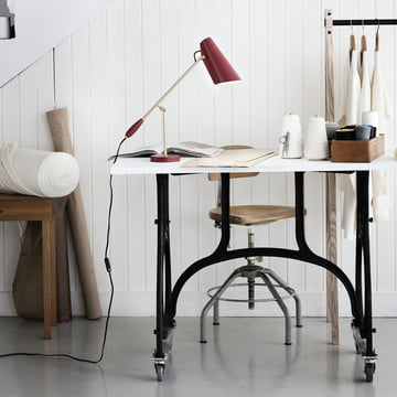 Northern Lighting - Lampe de table Birdy en marsala / laiton mat placée sur la table de travail