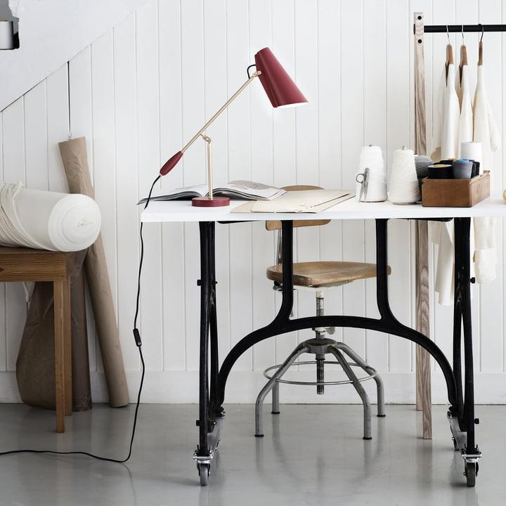 Northern Lighting - Lampe de table Birdy en marsala / laiton mat placée sur la table de travail